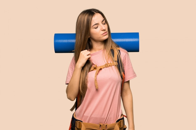 Young backpacker woman with tired and sick expression on isolated yellow background