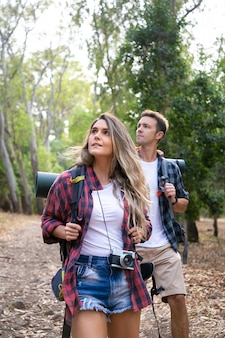 Giovani escursionisti escursionisti, godendo della vista e guardando il paesaggio nella foresta. viaggiatori attraenti caucasici che camminano sul sentiero nel bosco. concetto di turismo, avventura e vacanze estive con lo zaino in spalla