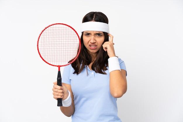 欲求不満と耳を覆っている孤立した白い背景の上の若いバドミントン選手の女性