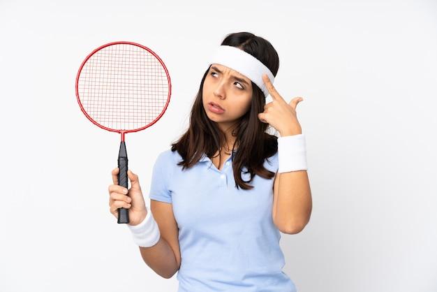 머리에 손가락을 넣어 광기의 제스처를 만드는 격리 된 흰색 배경 위에 젊은 배드민턴 선수 여자