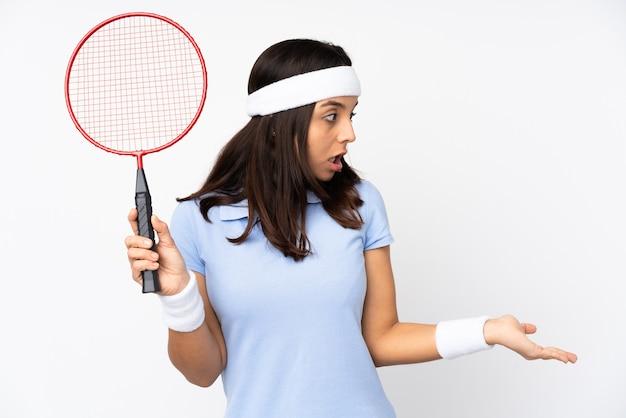 驚きの表情で孤立した白い背景の上の若いバドミントン選手の女性 Premium写真