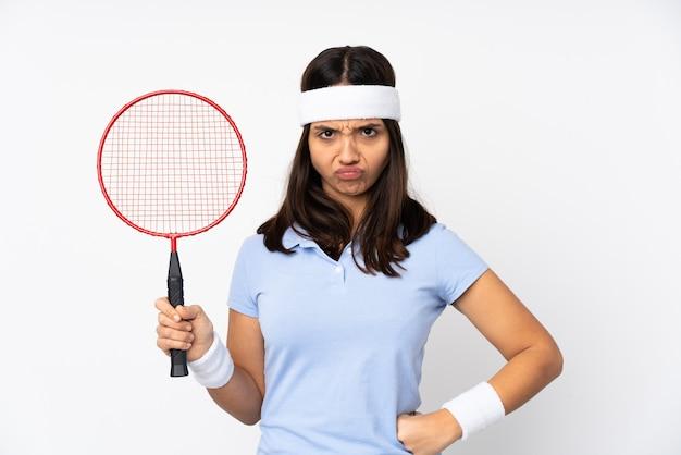 Молодая женщина-игрок в бадминтон над изолированной белой стеной сердится Premium Фотографии