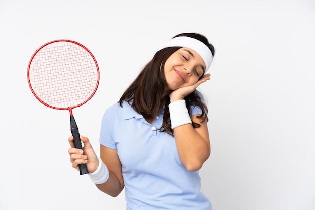 격리 된 흰 벽 dorable 식에서 수면 제스처를 만드는 젊은 배드민턴 선수 여자
