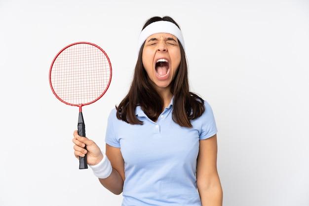 Молодая женщина-бадминтонистка над изолированной белой стеной кричит вперед с широко открытым ртом