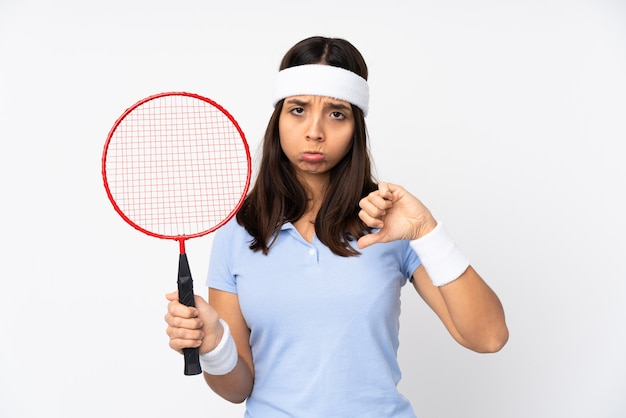 Young badminton player woman over white wall showing thumb down with negative expression