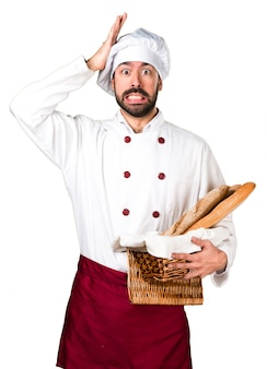 いくつかのパンを持っていると疑問を持っている若いパン屋