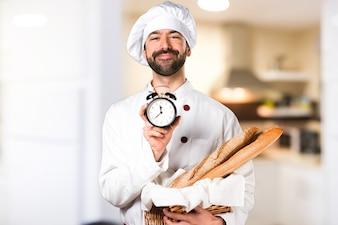 いくつかのパンを保持し、ヴィンテージ時計をキッチンで保持する若いパン屋
