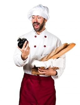 いくつかのパンを保持し、ヴィンテージ時計を保持する若いパン屋