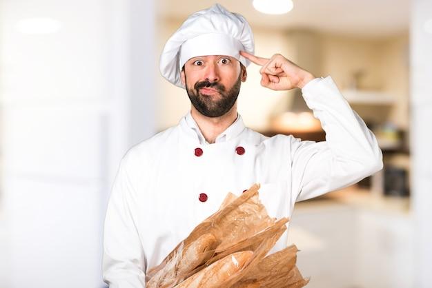 いくつかのパンを保持し、キッチンで狂ったジェスチャーを作る若いパン屋