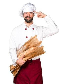 いくつかのパンを保持し、クレイジーなジェスチャーを作る若いパン屋