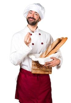 Молодой пекарь, держащий хлеб и делая денежный жест
