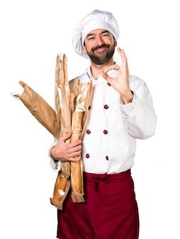 Молодой пекарь, держащий хлеб и делая знак ок