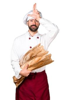 Молодой пекарь, держащий хлеб и делая глупый знак