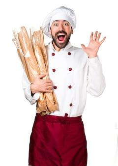 いくつかのパンを保持し、驚きジェスチャーを作る若いパン屋
