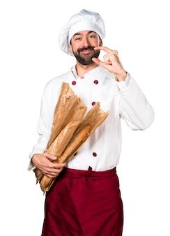 Молодой пекарь, держащий хлеб и делая маленький знак