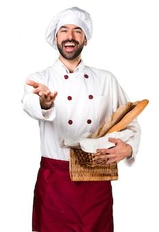 Молодой пекарь, держащий хлеб и представляющий что-то