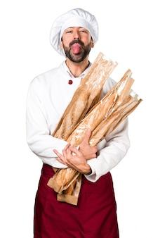 Молодой пекарь держит хлеб и вынимает язык