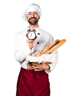 Young baker holding some bread and holding vintage clock