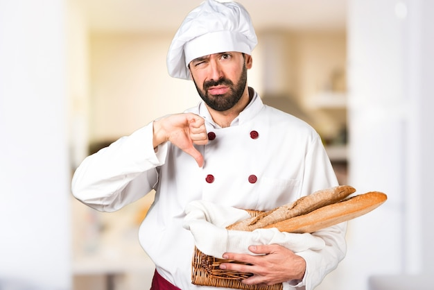 Young baker holding some bread and making bad signal in the kitchen