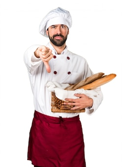 Young baker holding some bread and making bad signal