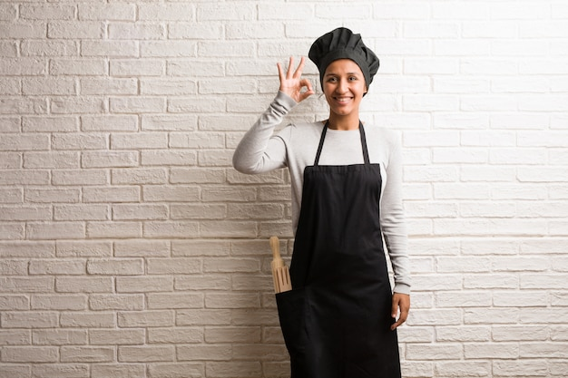 Young baker indian woman against a bricks wall cheerful and confident doing ok gesture.