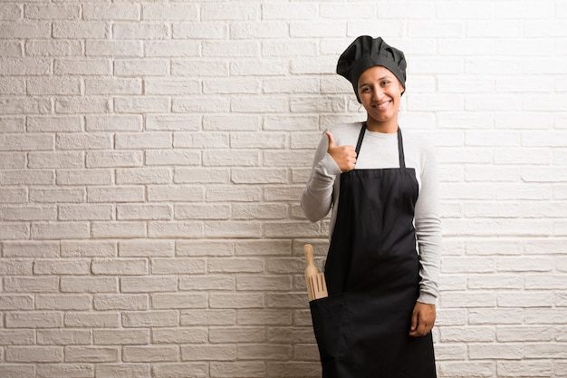 Young baker indian woman against a bricks wall cheerful and excited, smiling and raising her thumb up