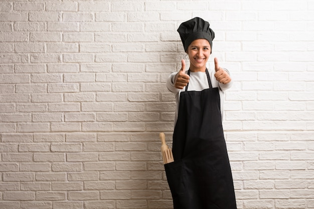 Young baker indian woman against a bricks wall cheerful and excited.