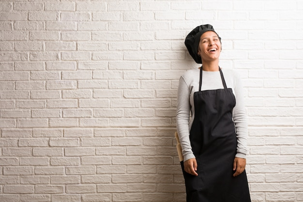 Young baker indian woman against a bricks wall cheerful and with a big smile