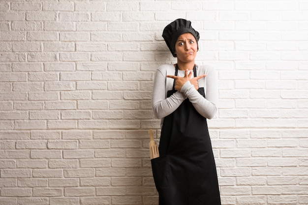 Young baker indian woman against a bricks wall confused and doubtful