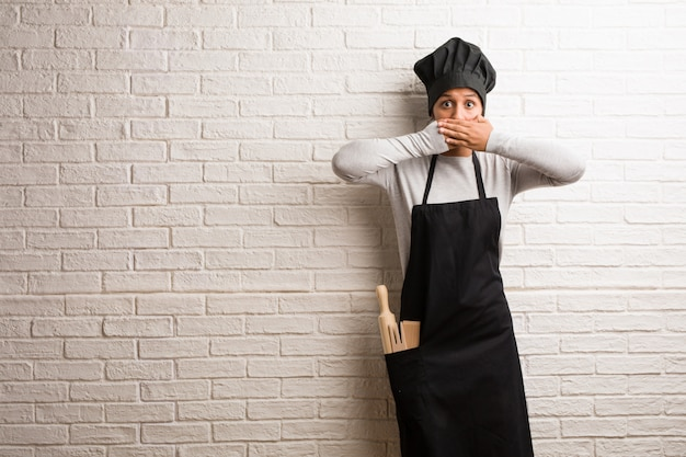 Young baker indian woman against a bricks wall covering mouth, symbol of silence and repression