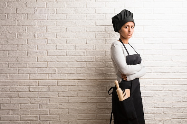 Young baker indian woman against a bricks wall crossing his arms, serious and imposing.