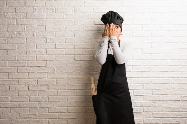 Young baker indian woman against a bricks wall feels worried and scared, looking and cover