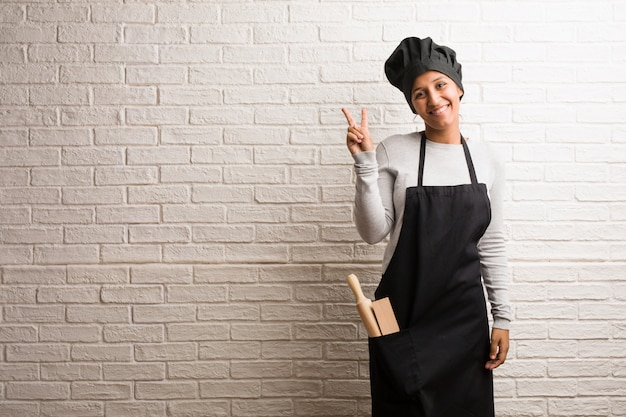 Young baker indian woman against a bricks wall fun and happy, positive and natural