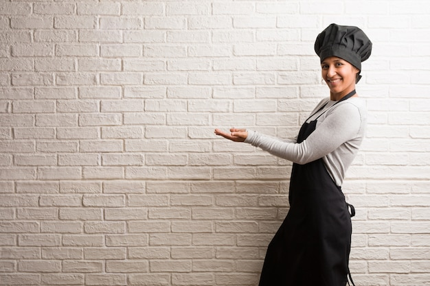 Young baker indian woman against a bricks wall holding something with hands