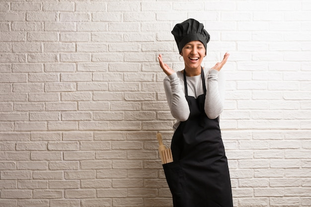 Young baker indian woman against a bricks wall laughing and having fun, being relaxed and