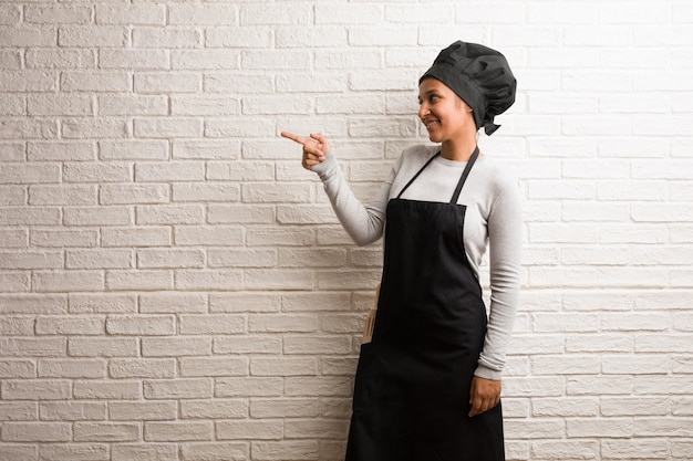 Young baker indian woman against a bricks wall pointing to the side.