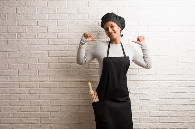 Young baker indian woman against a bricks wall proud and confident