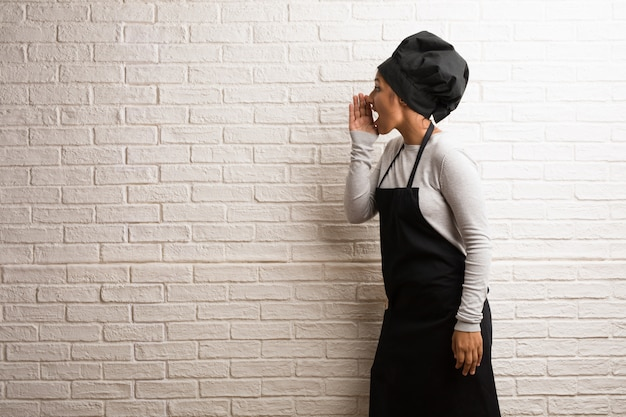 Young baker indian woman against a bricks wall screaming angry