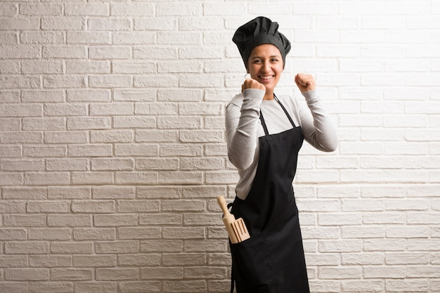 Young baker indian woman against a bricks wall very happy and excited