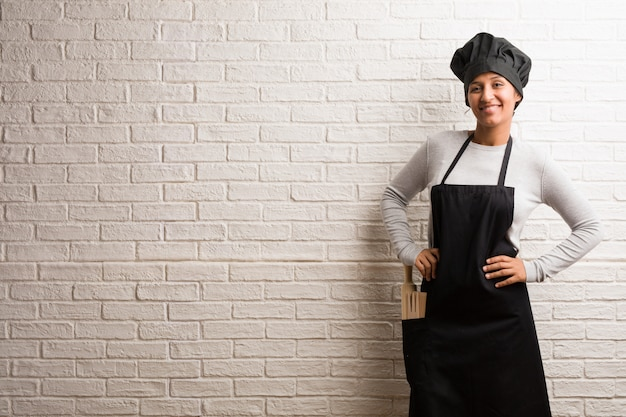 Young baker indian woman against a bricks wall with hands on hips, standing, relaxed and s