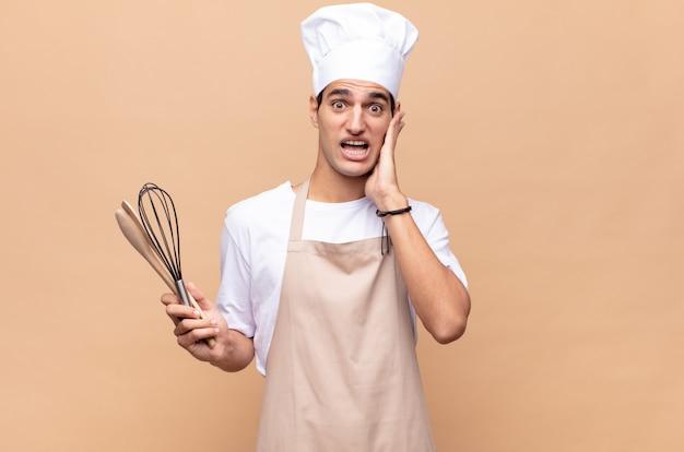 幸せ、興奮、驚きを感じ、顔を両手で横に見ている若いパン屋の男