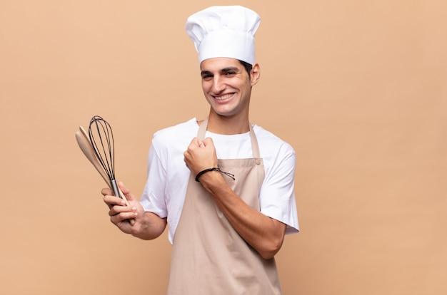 挑戦に直面したり、良い結果を祝ったりするときに、幸せで、前向きで、成功し、やる気を感じている若いパン屋の男