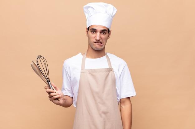Молодой пекарь выглядел озадаченным и сбитым с толку, нервно закусив губу, не зная ответа на вопрос