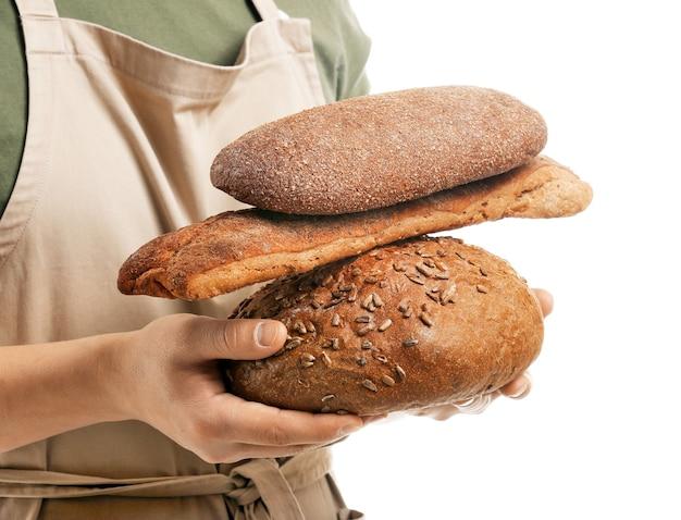 Молодой пекарь со свежим хлебом на белом, крупным планом
