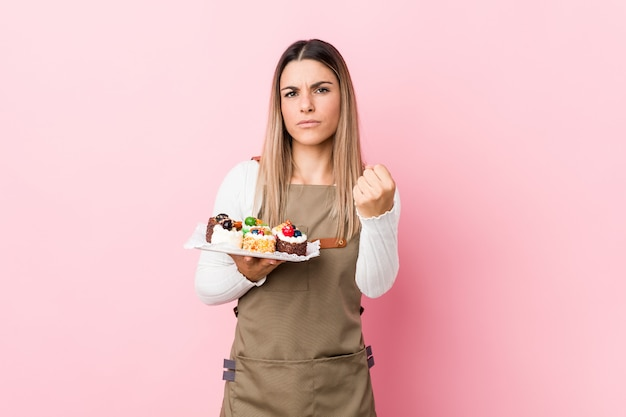 Young baker woman holding sweets showing fist to with aggressive facial expression.