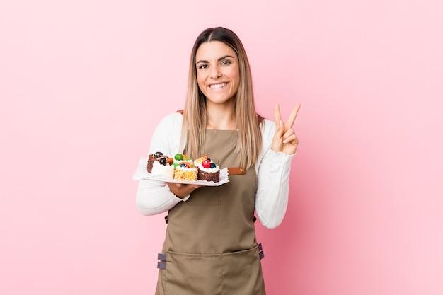 指で2番目を示すお菓子を保持している若いパン屋の女性。