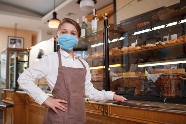 그의 가족 빵집에서 자랑스럽게 포즈를 취하는 의료 마스크를 쓰고 젊은 제빵사 아들