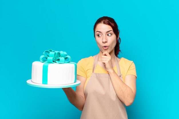 Young bakery employee woman with a birthday cake