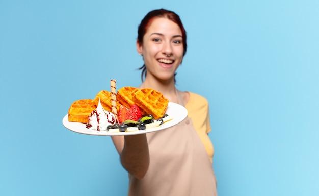 와플과 케이크를 가진 젊은 빵집 직원 여자
