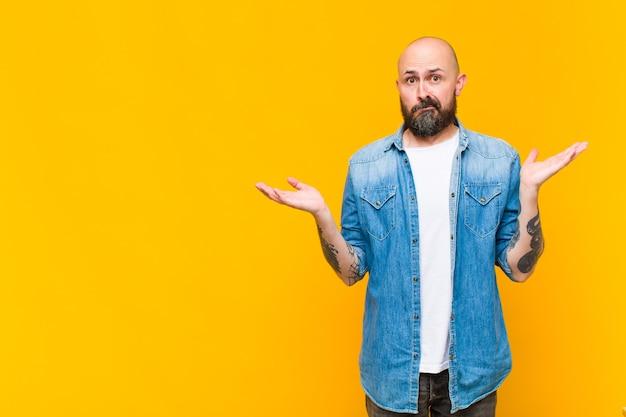 젊은 대머리와 수염 난 남자가 의아해하고 혼란스럽고 의심스럽고 가중하거나 재미있는 표현으로 다른 옵션을 선택하는 느낌